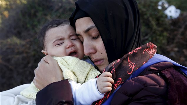 A Syrian refugee woman wearing a black headscarf and a purple winter coat hugs her crying baby after arriving on a raft on the Greek island of Lesbos.