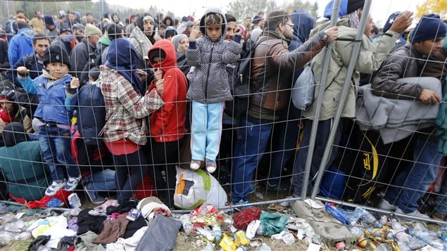 Children climb on a fence as migrants queue to cross the border into Spielfeld in Austria from the village of Sentilj, Slovenia, October 28, 2015.