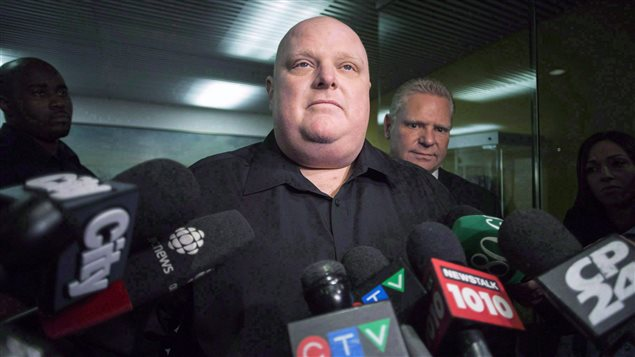 Sombre-looking former Toronto mayor Rob Ford stands next to his brother Doug Ford outside his office as he scrums with the media in Toronto on November 21, 2014.