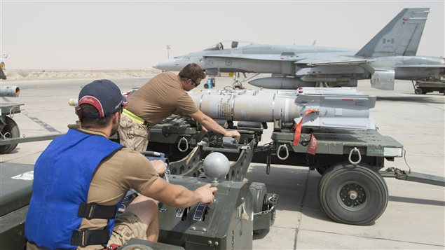 Royal Canadian Air Force Air Weapon Systems Technicians, deployed as part of Air Task Force – Iraq, prepare munitions for loading to a CF-188 Hornet, at the Camp Patrice Vincent flight line in Kuwait, during Operation IMPACT on August 1, 2015. (Photo: OP IMPACT, DND)