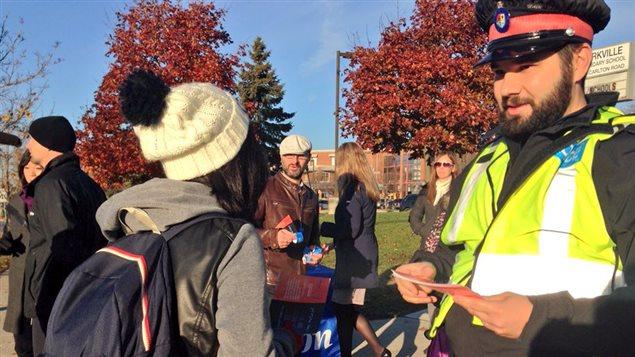 Un policier distribue des réflecteurs à des élèves en Ontario.
