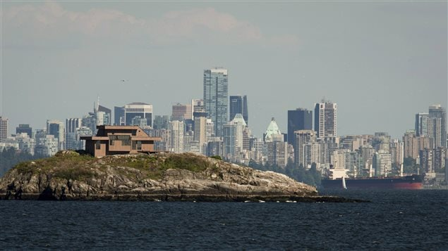 Downtown Vancouver is seen in the background as a house sits on top of a small island in West Vancouver, B.C., on June 10, 2013. Vancouver is the second most unaffordable housing market in the world after Hong Kong, according to a new study of major property markets.