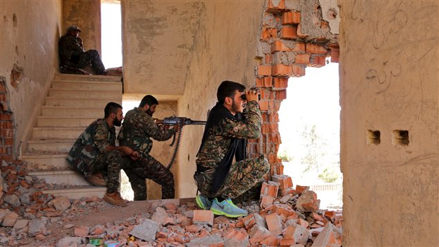 Kurdish People's Protection Units (YPG) fighters take up positions inside a damaged building in Ghwayran neighborhood in Hasaka city, Syria July 22, 2015.