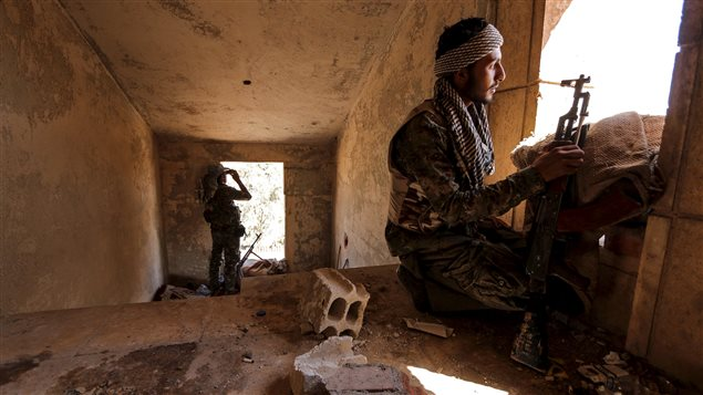 A Kurdish People's Protection Units (YPG) fighter takes up position inside a damaged building in Hasaka city, Syria July 22, 2015.