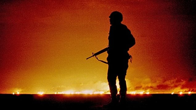 A U.S. soldier stands night guard near the Iraq border in February 1991 as oil wells, set alight by retreating Iraqi soldiers, burn in Kuwait.