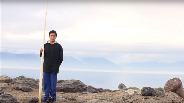 An Inuit boy stands with a narwhal tusk on the shores of Tallurutiup Tariunga (Lancaster Sound)