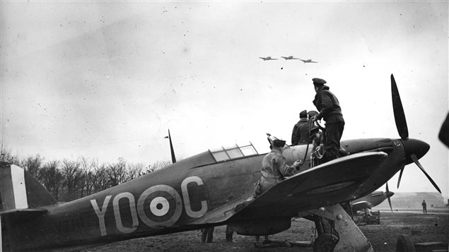 A Hurricane is re-armed while a section flies overhead. From the photo album of Flying Officer R.W.G. Norris, from Saskatoon, Saskatchewan, who served with No. 1 Squadron during the Battle of Britain. IT was this type of fighter that Gill was piloting when attacked by four Japanese fighters and shot down and killed in 1943.