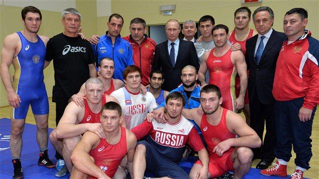 Vladimir Poutine, au centre, avec le ministre des Sports Vitaly Mutko, � droite, en compagnie d'athl�tes russes.