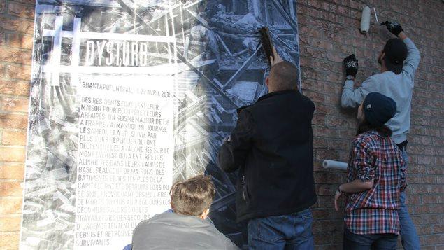 L'équipe de Dysturb colle une photo du Népal sur un mur du Mile-End.