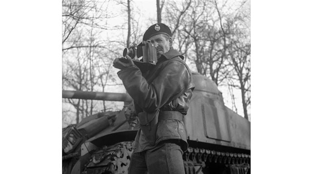 Lieutenant H. Gordon Aikman of the Canadian Army Film and Photo Unit, holding an Anniversary Speed Graphic camera. Vught, Netherlands, February 1, 1945