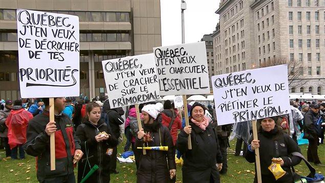 Des syndiqués du secteur public manifestent en brandissant des pancartes témoignant de leur exaspération.
