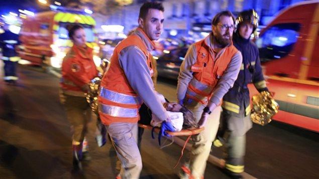 Les ambulanciers évacuent une femme du théâtre Bataclan à Paris.