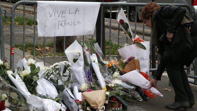 Une femme déposes fleurs devant le Bataclan, où plus d'une centaine de personnes ont été tuées.