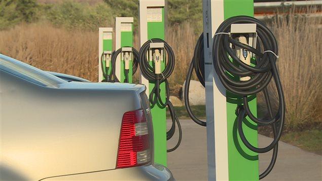 Des voitures à essence garées devant des bornes de recharge pour voitures hybrides