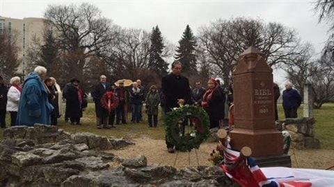 Des citoyens du Manitoba observe une minute de silence devant la tombe de Louis Riel.