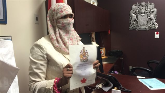 Zunera Ishaq holds her citizenship certificate after swearing the oath on Friday afternoon. She started wearing a niqab at age 15, against her family's wishes. (Sylvia Thomson/CBC)