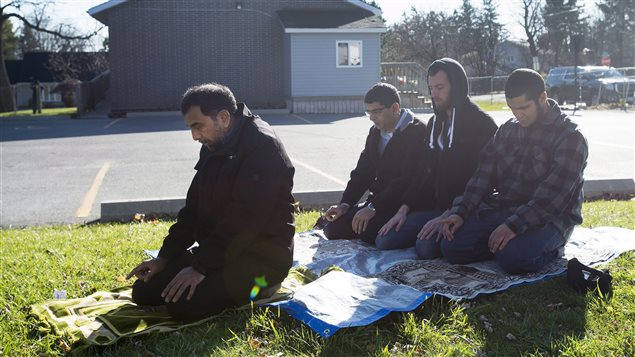 A group of men pray outside of the mosque Masjid Al-Salaam in Peterborough, Ont., on Monday, November, 16, 2014.