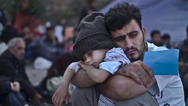 Un Syrien se repose avec son fils, tout juste arrivé en Grèce après un voyage en bateau de la Turquie. (archives)