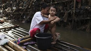 A mother bathes her child near a stack of rubbish in Ciliwung river in the Indonesian capital of Jakarta May 28, 2009.