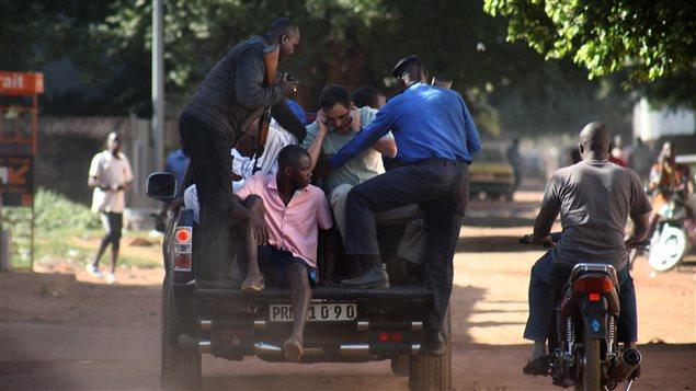 Des militaires maliens évacuent des otages de l'hôtel Radisson de Bamako.