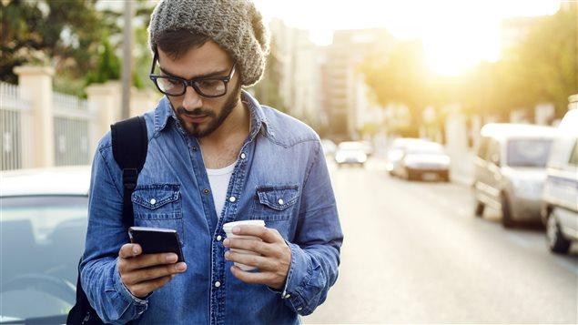 Un jeune homme consulte son téléphone, un café à la main.