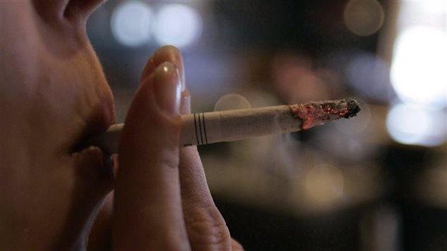 Une persomme fume une cigarette