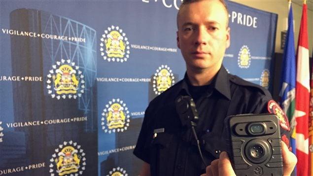Un policier de Calgary tient une radio à laquelle est intégrée une caméra.
