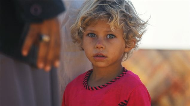 An internally displaced girl stands at a makeshift refugee camp in Sinjar town, in Idlib province, Syria November 20, 2015.