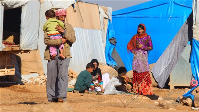 Internally displaced Syrians stand outside tents at a makeshift refugee camp in Sinjar town, in Idlib province, Syria November 20, 2015.