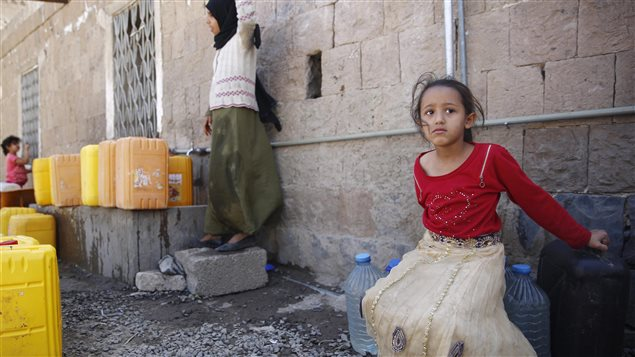 A young girl guards the water buckets she fetched amid an acute shortage in Sanaa, Yemen on Nov. 25, 2015.