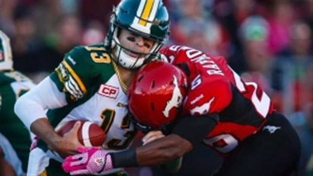 Edmonton Eskimos' quarterback Mike Reilly, left, is sacked by Calgary Stampeders' Keon Raymond during a game on Saturday, Oct. 10, 2015. Reilly has put up some pretty impressive numbers since returning to action for his Eskimos. A minor detail that many will miss, Canadian footballs hae the white stripes on them, American footblls do not (also ours are inflated properly ;-)