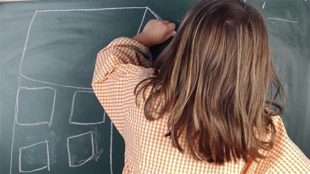 Une jeune gauchère dessine au tableau.