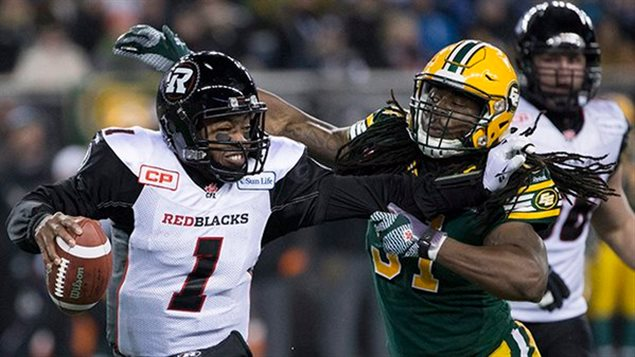 The Ottawa Redblacks quarterback fends off a tackle from an Edomonton Eskimos player. The Eskies won a close and exciting game 26-20. but now there are calls for the Eskimos to change the name of the long-standing franchise
