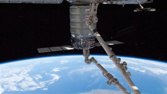 The Canadarm2 berths the Orbital Sciences Corp. Cygnus commercial cargo craft to the Harmony node of the International Space Station on Jan. 12, 2014. Earth's horizon and the blackness of space provide the backdrop for the scene.