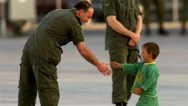 Un petit garçon kosovar serre la main d'un soldat canadien en 1999
