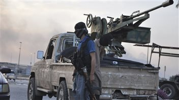 ISIS fighters stand guard at a checkpoint in the Iraqi city of Mosul on June 11, 2014.
