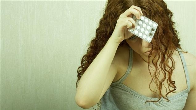 Une femme tenant des comprimés d'antidépresseurs