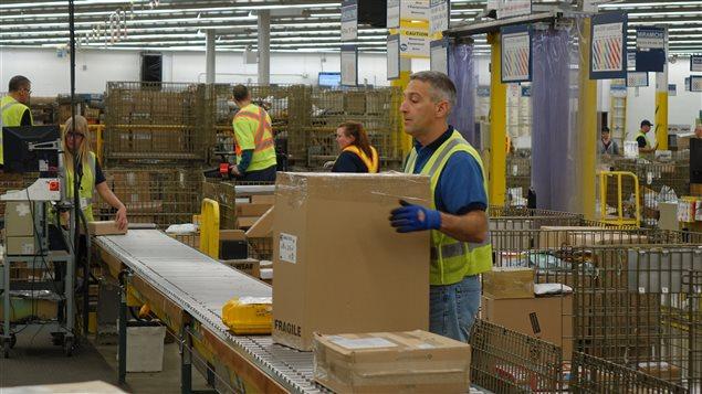 Des employés de Postes Canada travaillent au centre de distribution de Dieppe, au Nouveau-Brunswick.