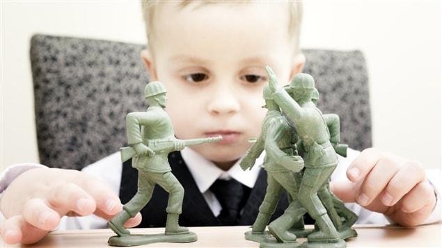 Un enfant joue à la guerre avec des figurines.