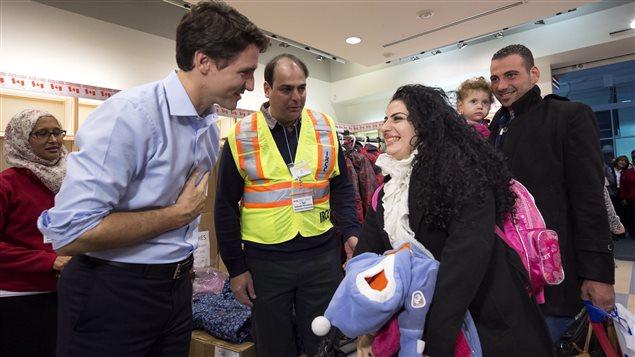 Le premier ministre Justin Trudeau accueille les premiers réfugiés syriens arrivés dans un vol nolisé à l'aéroport Pearson de Toronto.