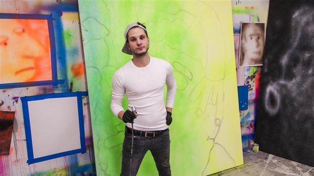 Austin Lee posant devant l'une de ses oeuvres