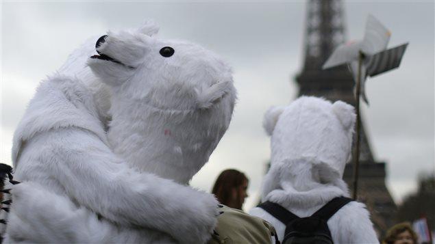 Deux ours polaires s'enlacent devant la ttour Eiffel à Paris.