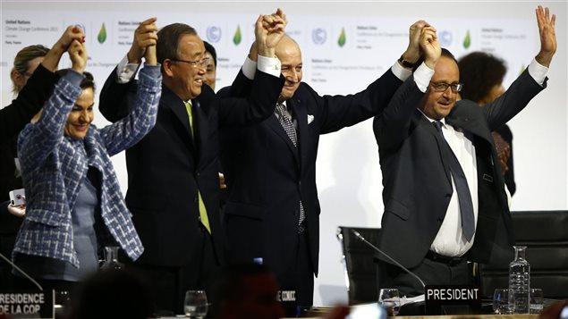 Christiana Figueres, secrétaire exécutive de la Convention-cadre des Nations unies sur les changements climatiques, Ban Ki-moon, secrétaire général des Nations unies, Laurent Fabius,  président de la conférence de Paris, et François Hollande, président de la République française, célèbrent la conclusion d'un accord sur le climat.