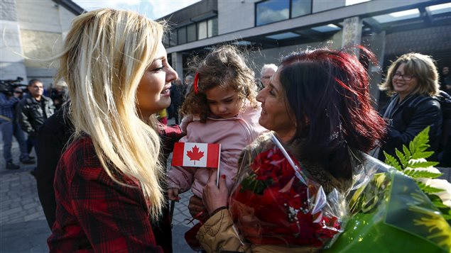 Maria Karageozian (L) and her daughter Rita (C) is reunited with her mother Elo Manushian, a Syrian refugee who arrived earlier in the morning at the Armenian Community Centre of Toronto in Toronto, December 11, 2015.