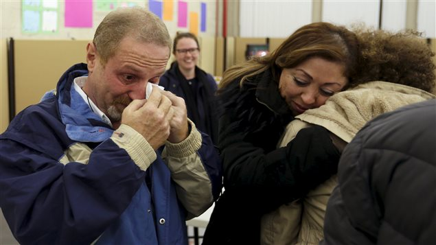 Syrian refugee Samer Beylouneh (L) wipes away tears as his sister and sponsor Marie Belona hugs his daughter Laila at the Welcome Centre in Montreal, Quebec, December 12, 2015.