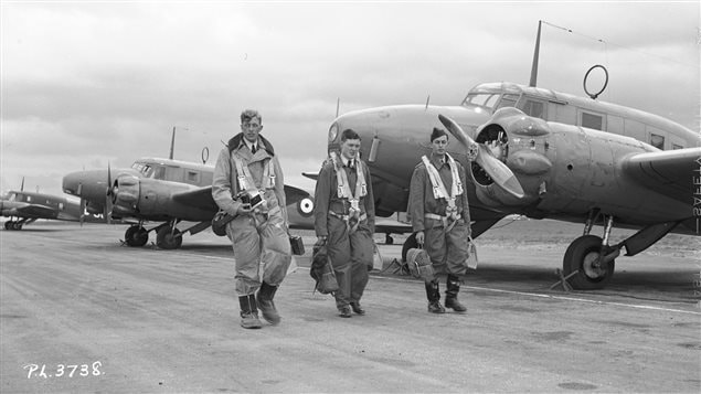 Observers from Australia, Canada and Great Britain walk to their Avro Anson aircraft for navigation training at RCAF Rivers, Manitoba. Twin Engine planes were used for training of bomber pilots, and navigators.