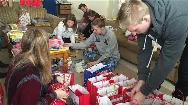 Quelques heures avant la fête de Noël organisée pour une soixantaine d'enfants réfugiés, les Canadiens emballent tous les cadeaux.