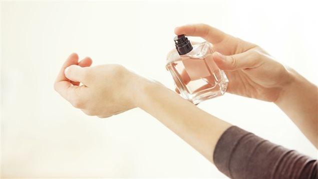 Une femme teste un parfum sur son bras.