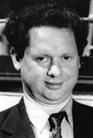 We see Dylan Thomas from the shoulders up. He wears a suit and his tie is slightly askew. He has pale skin and dark and somewhat curly hair. A slight smile creases his lips.