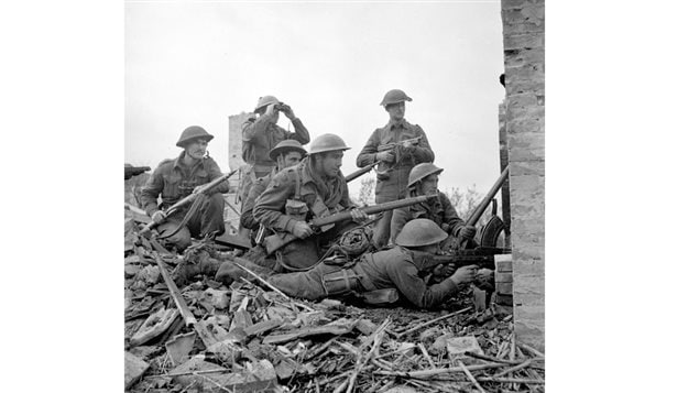 Canadian soldiers in Ortona in December getting ready to advance through a breached wall during the vicious house to house fighting. A variety of weapons from the Bren LMG, to a Thampson submachine gun to the standard bolt action Lee Enfield.